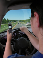 person driving and using a cell phone