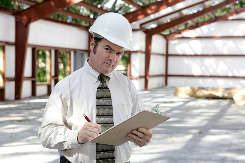 safety inspector wearing a hard had and holding a clipboard