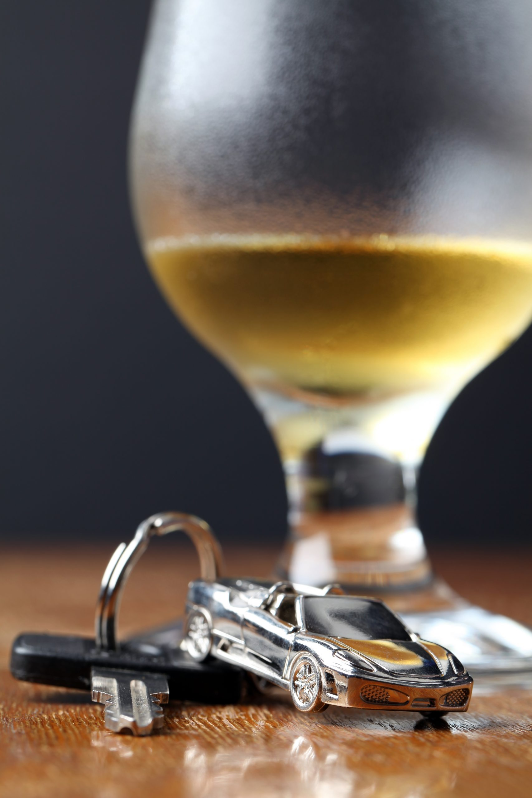 key chain with a miniature car and a glass of beer in the background