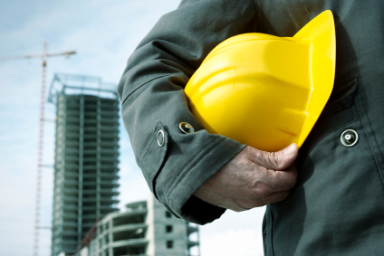 person holding a yellow hard hat under the arm