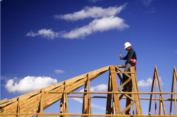 construction man hammering on the frame of a roof