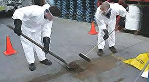 two people wearing hazmat suits cleaning up a spill