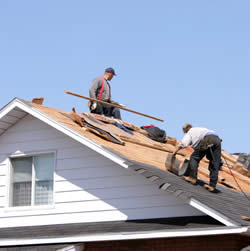 men working on the roof of a house