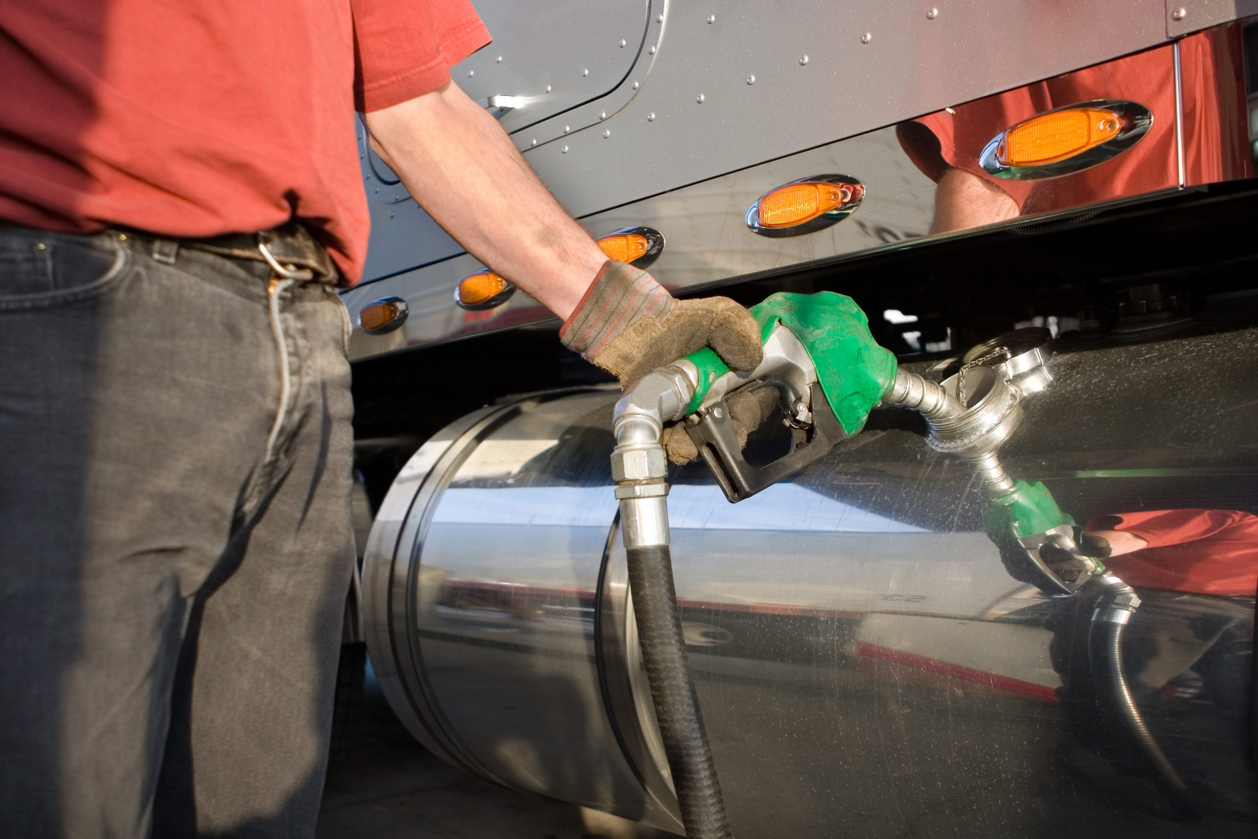 A man fueling a gas tank of a truck