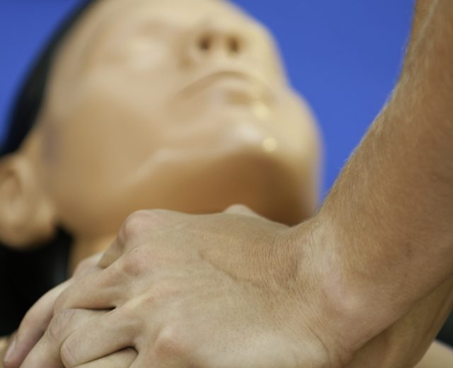 hands on a CPR training dummy