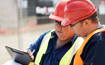 two construction men looking at a tablet