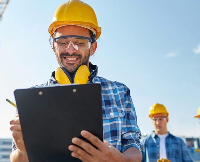 smiling construction man holding a clipboard