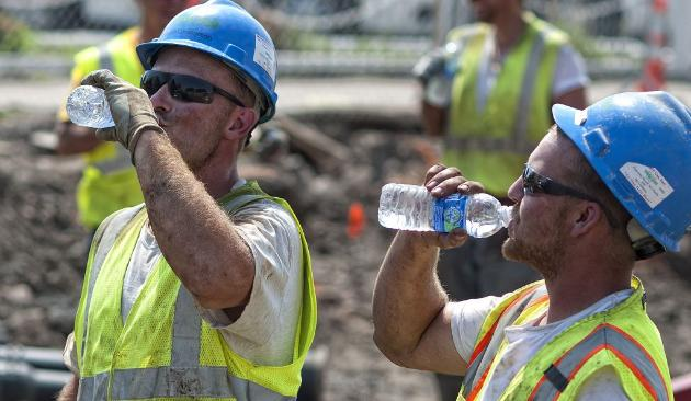 sweating construction workers drinking bottles of water