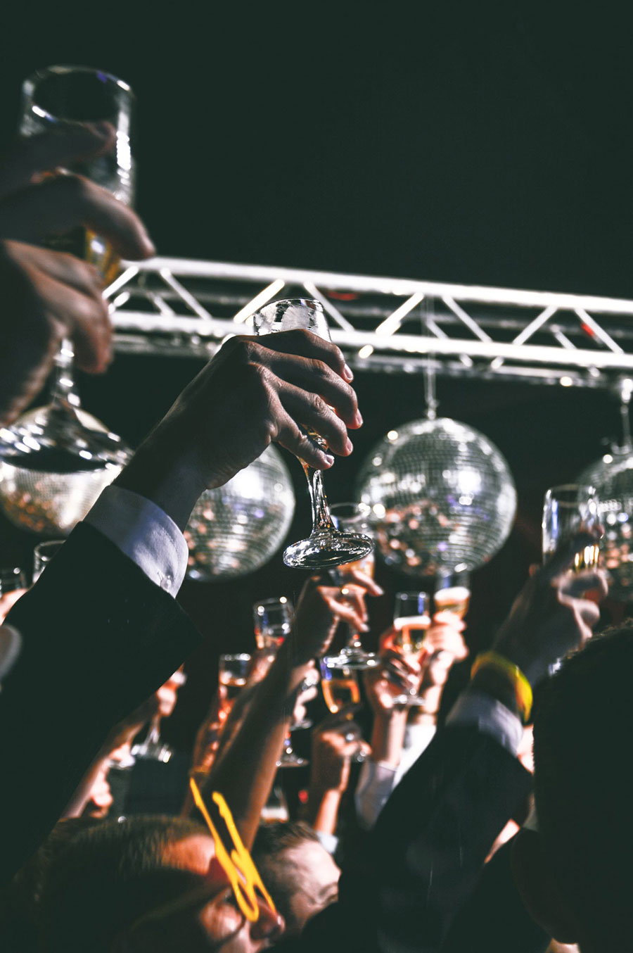 people holding up glasses for a group toast