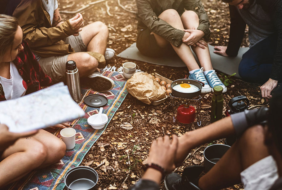 group of people safely cooking while camping