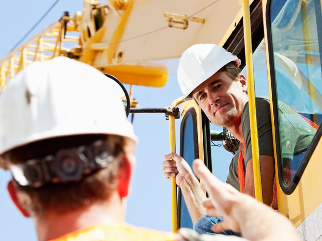 construction workers in and near heavy mobile equipment