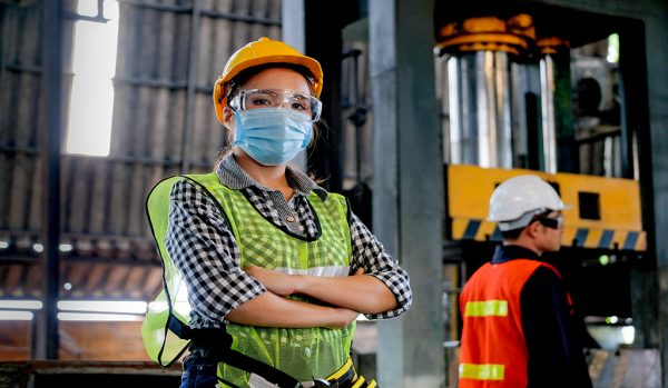 Factory woman technician with hygienic mask stand with confident action with her co-worker as background