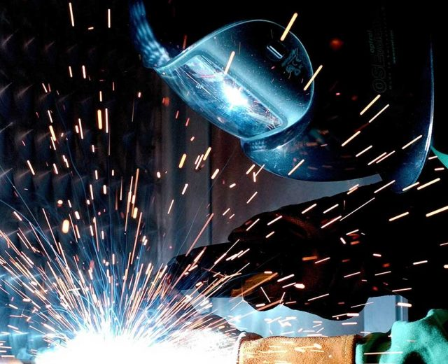 person working with hot melding with sparks flying