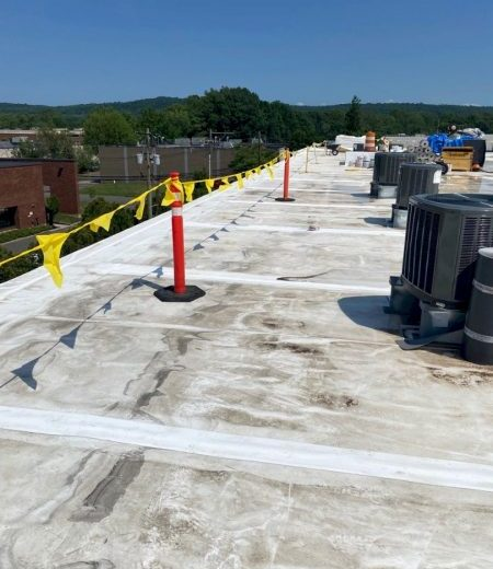 commercial building roof with construction safety warning line marked by flags