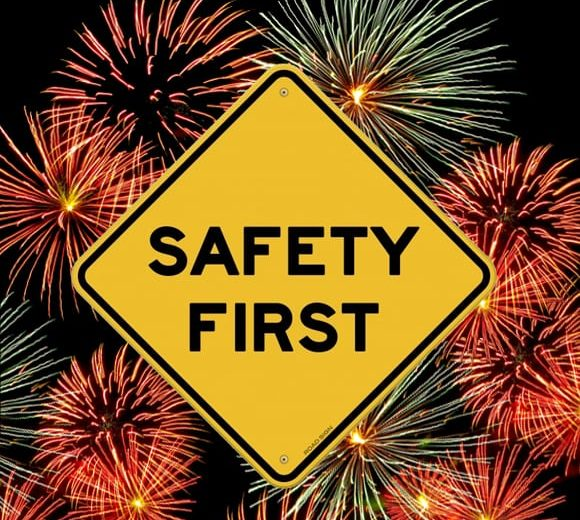 sign reads safety first with fireworks in the background