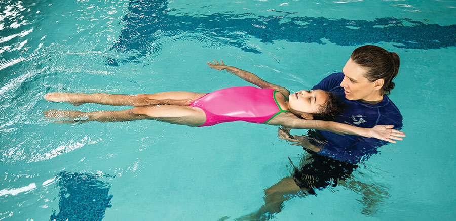 woman giving a young girl swimming lesson