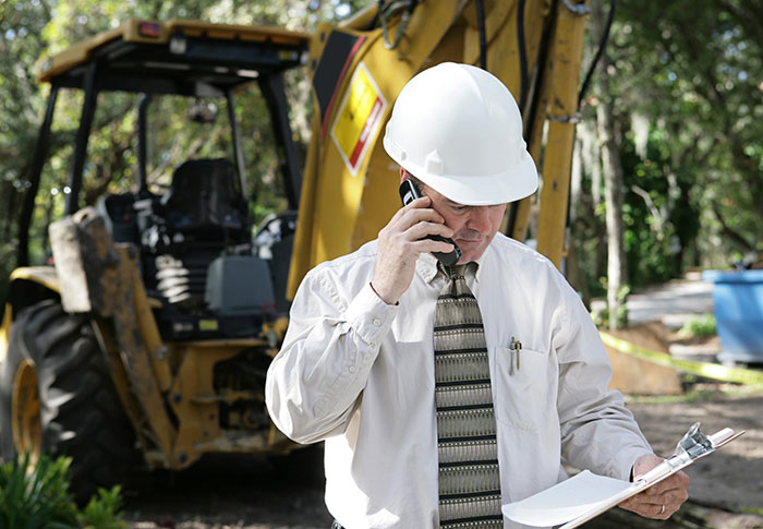 ohsa safety inspector holding a clipboard on a cell phone