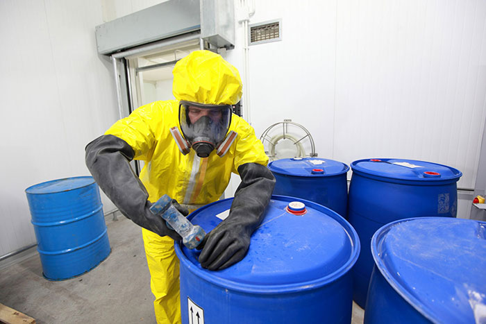 Professional in uniform working with chemical containers