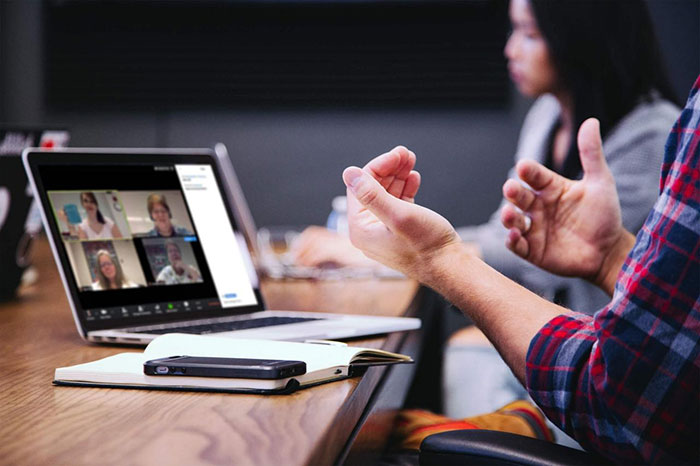 computer on a conference table showing a group video conference call