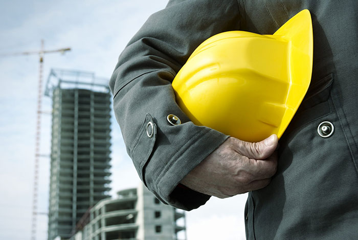 arm holding a construction hard hat with a high rise building in the background
